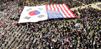 South Korean and U.S. flags spread out among a large gathering of people (© Ahn Young-joon/AP Images)