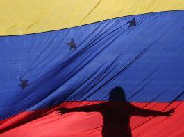 Two people in silhouette behind Venezuelan flag (© Fernando Llano/AP Images)