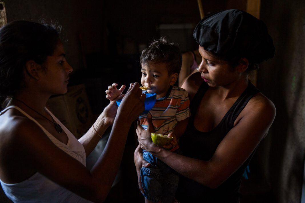 Mulher alimenta bebê que está nos braços de outra mulher (© Rodrigo Abd/AP Images)