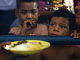 Two small children looking at bowl of food (© Eraldo Peres/AP Images)