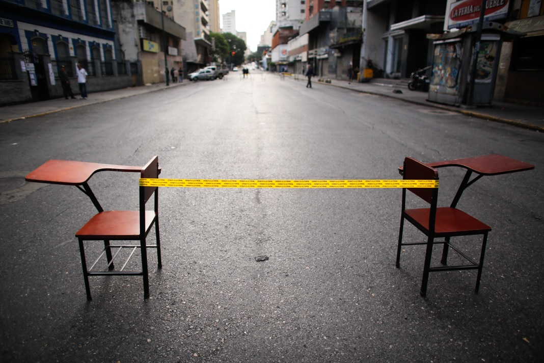 Yellow tape strung between two school desks (© Ariana Cubillos/AP Images)