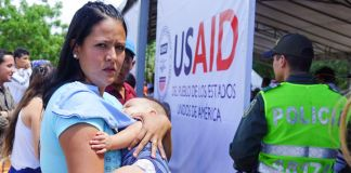 Woman standing by USAID sign holding baby (© Christine Armario/AP Images)