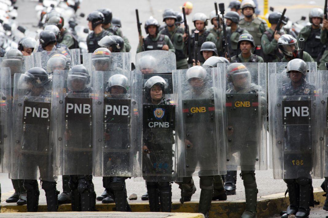 Policía venezolana antidisturbios en una fila (© Ariana Cubillos/AP Images)