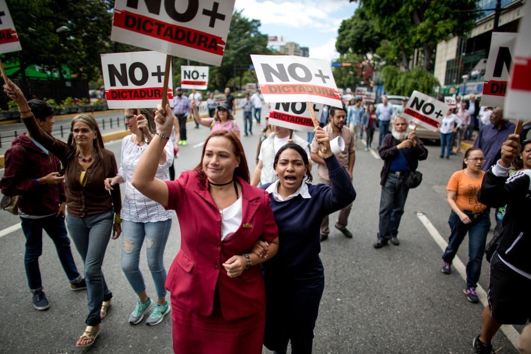 Protesters in the street holding signs (© Ariana Cubillos/AP Images)