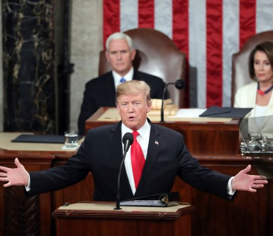 President Trump at lectern, Vice President Pence and Nancy Pelosi sitting behind him (© Andrew Harnik/AP Images)