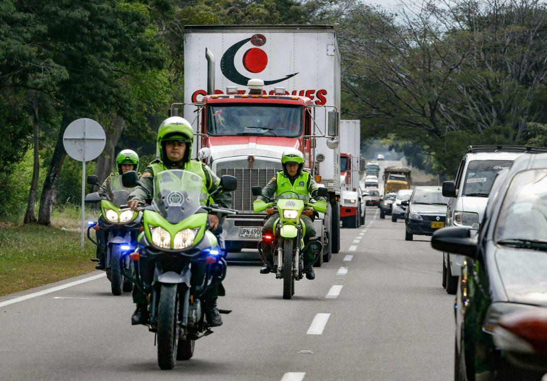 Police on motorcycles escort trucks on a highway (© Fernando Vergara/AP Images)