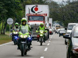 Police on motorcycles ahead of trucks on highway (© Fernando Vergara/AP Images)