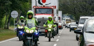 Police on motorcycles escort trucks on a highway (© Fernando Vergara/AP Images)