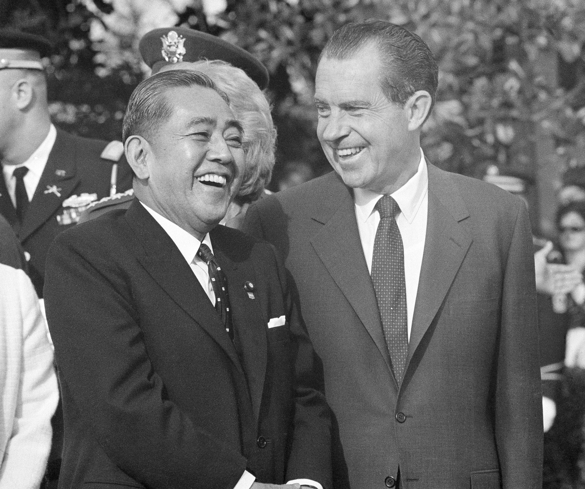 Japanese Prime Minister Eisaku Sato and U.S. President Richard Nixon standing and smiling (© AP Images)