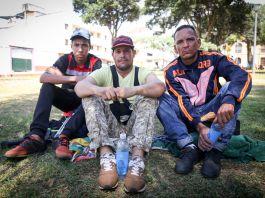 三名委内瑞拉男子坐在草地上(Alison Harding/USAID/OFDA)