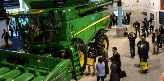 People looking at a large green tractor inside an exhibit hall (© Robert Lever/AFP/Getty Images)