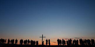 Siluet orang-orang saat kebaktian Paskah saat matahari terbit (© Jessica Rinaldi / The Boston Globe / Getty Images)
