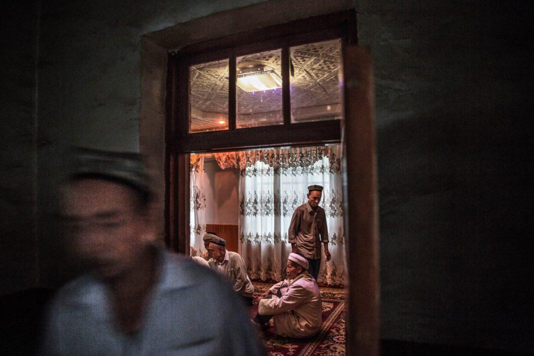 Vista de una casa en la que hay personas de pie y otras sentadas (© Kevin Frayer/Getty Images)