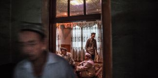 View into home where people are sitting and standing (© Kevin Frayer/Getty Images)