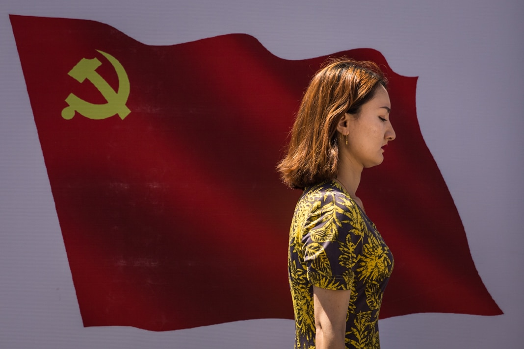 Woman walking past painting of red flag featuring hammer and sickle (© Wang HE/Getty Images)