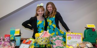 2 young girls showing off their lemonade stand and wares (© Lemonade Day)