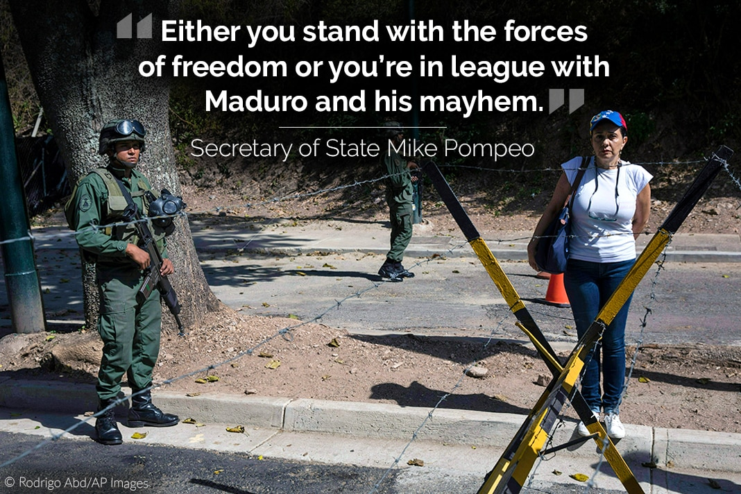 Armed soldiers, barbed wire fence and woman nearby, with quote from Secretary Pompeo overlaid (© Rodrigo Abd/AP Images)