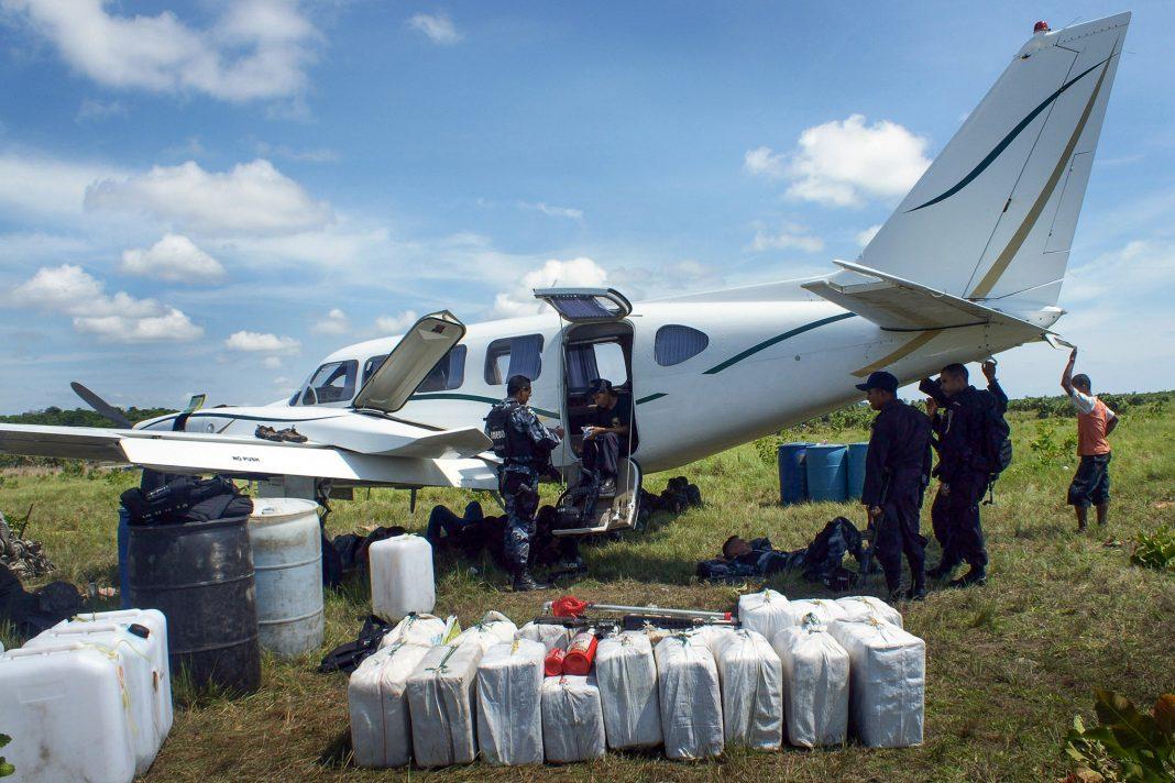 Pequeno avião no campo com pessoas em pé nas proximidades e carga no chão (© Reuters/polícia hondurenha/ajuda humanitária)