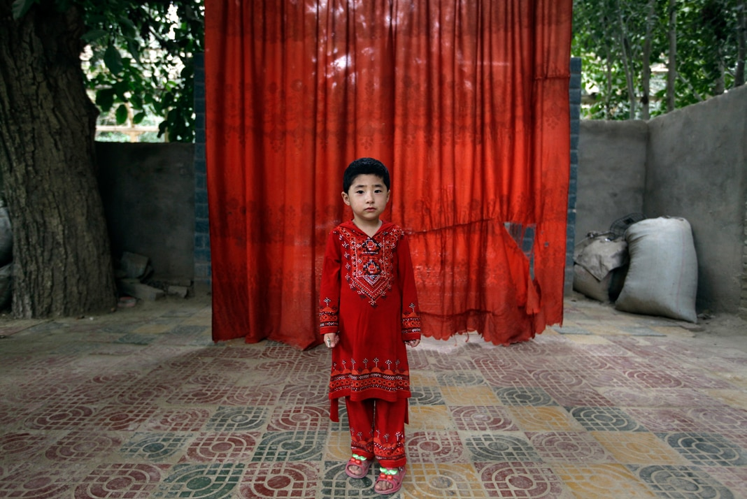 Child dressed in red standing in front of red curtain (© Stringer/Reuters)