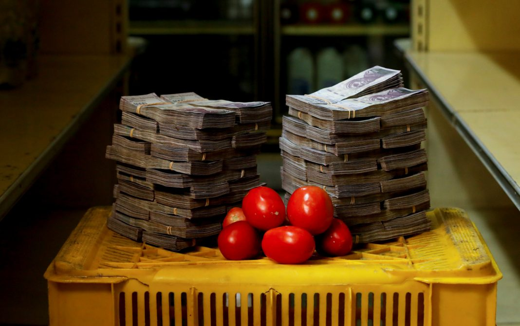 A stack of tomatoes sitting in front of two tall stacks of cash (© Carlos Garcia Rawlins/Reuters)