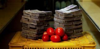 Des tomates posées sur une caisse, entre deux grands tas de billets de banque (© Carlos Garcia Rawlins/Reuters)
