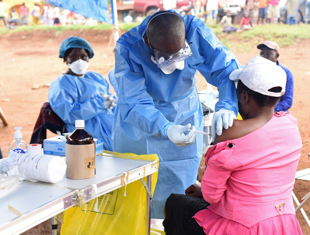 Health worker administering vaccine (© Olivia Acland/Reuters)