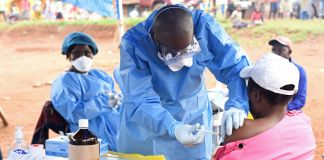 Un soignant administrant un vaccin (© Olivia Acland/Reuters)