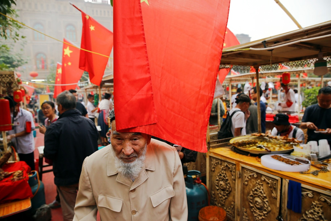 Man walking under red flags in open-air market (© Thomas Peter/Reuters)