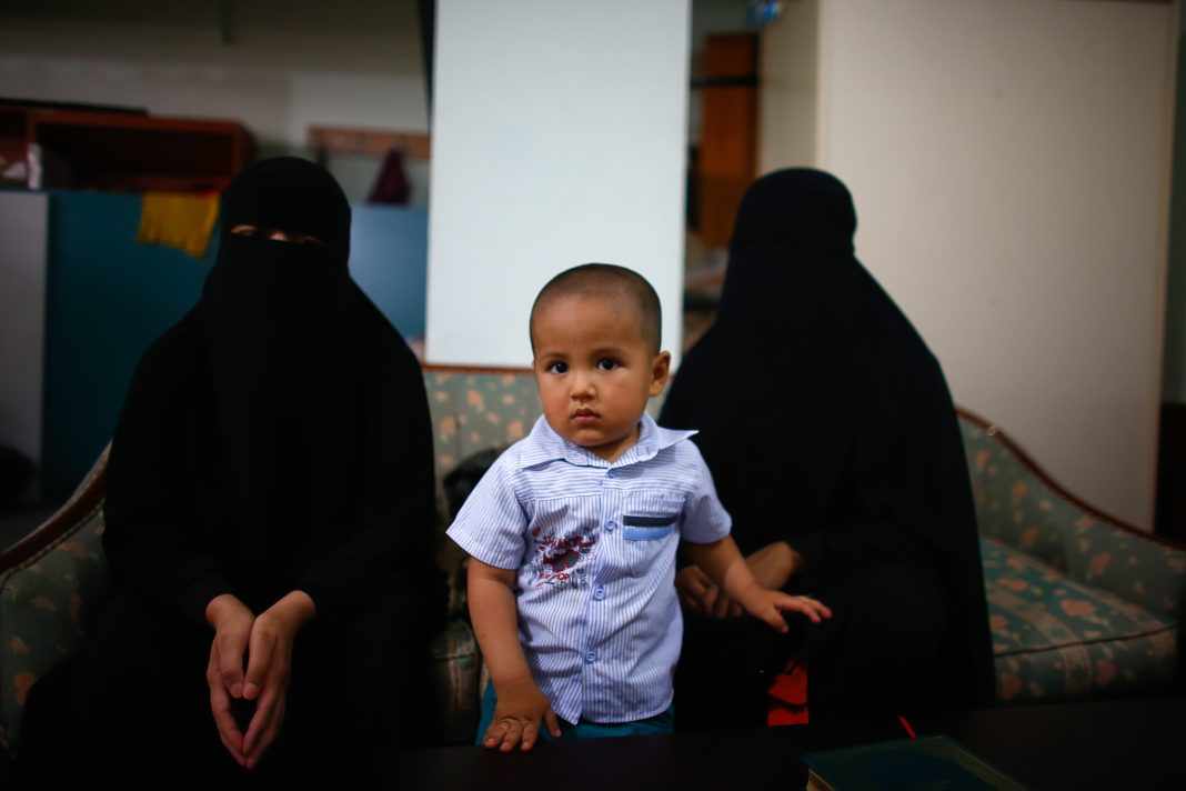 Child standing between two be-robed women (© Osman Orsal/Reuters)