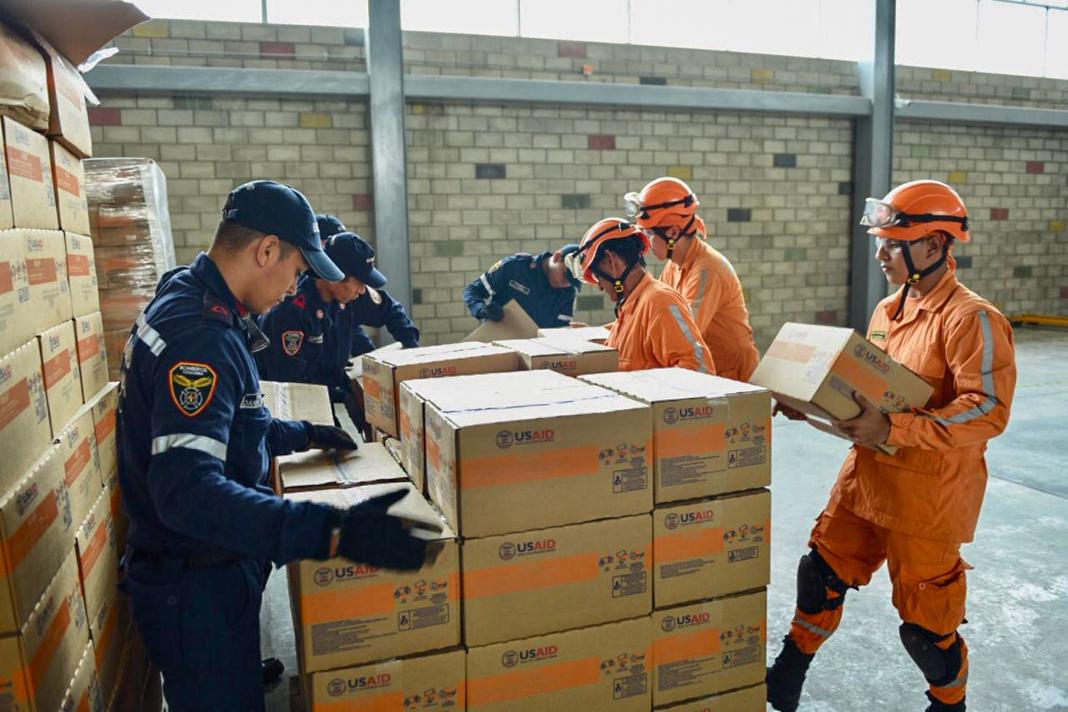 Workers handling boxes in large stacks (U.S. Embassy Bogotá)
