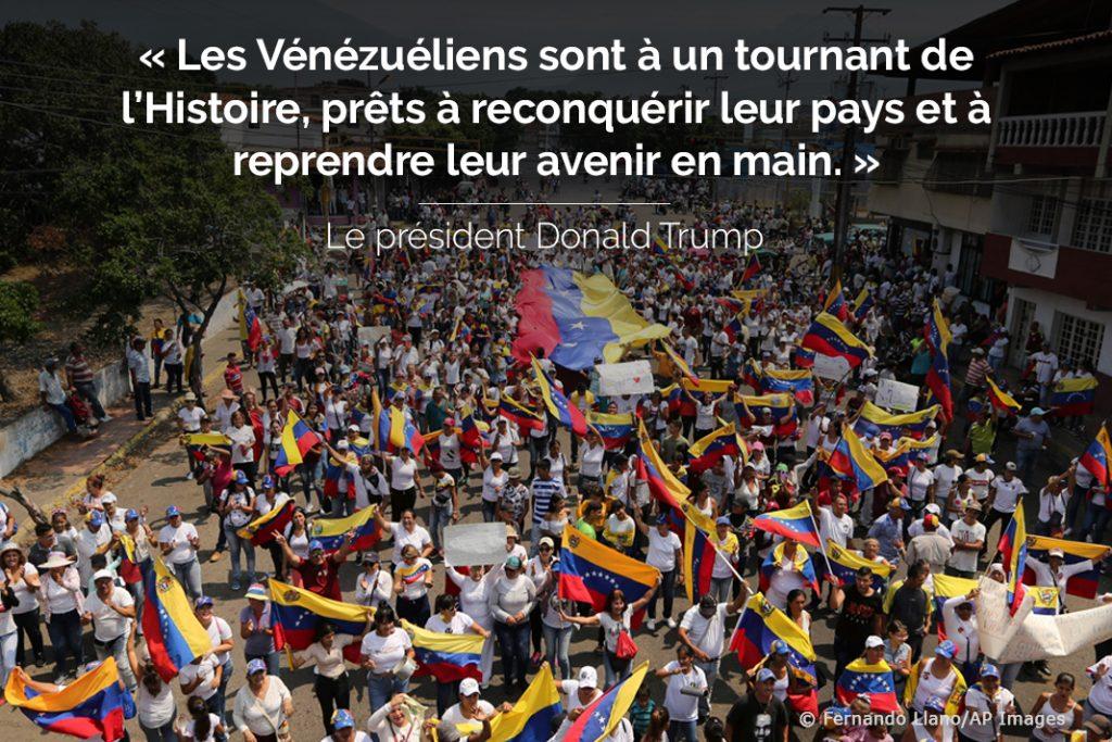 Photo d'une foule brandissant des drapeaux vénézuéliens avec une citation du président Trump (© Fernando Llano/AP Images)