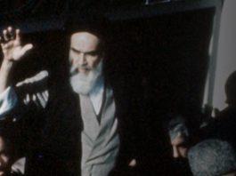 Ayatollah Khomeini, with raised hand