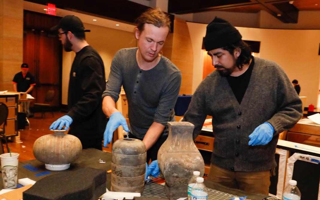Des hommes portant des gants de travail, en train de déplacer soigneusement des objets d'art (© Sam Riche)