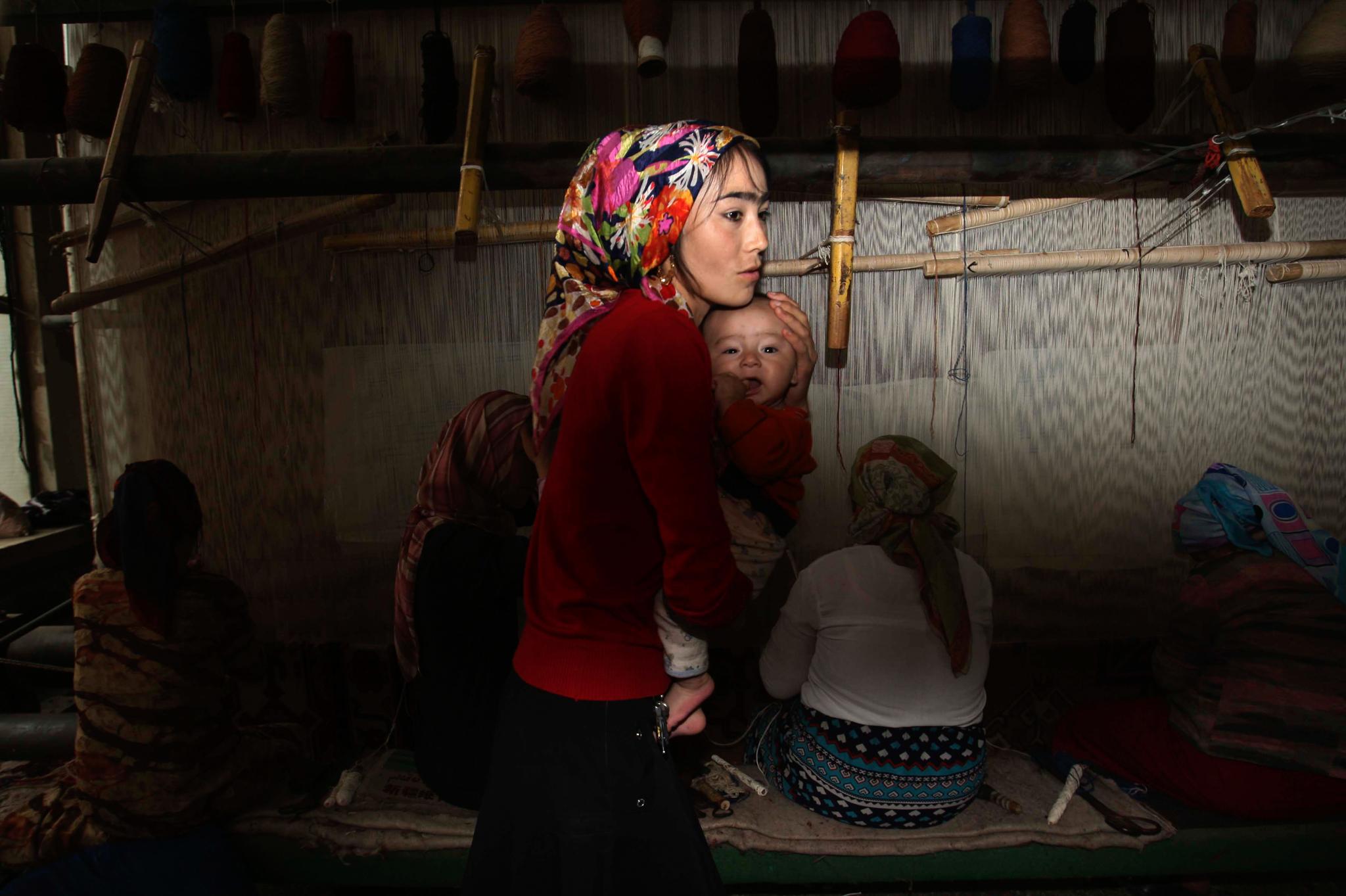 Woman holding baby (© Elizabeth Dalziel/AP Images)
