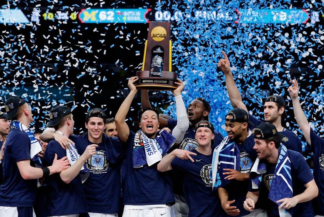 Atletas seguram troféu junto a chuva de confetes azuis (© David J. Phillip/AP Images)