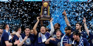 Athletes holding up a trophy as blue confetti comes down on them (© David J. Phillip/AP Images)