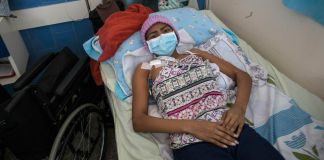 Patient wearing health mask lying on bed in hospital (© Rodrigo Abd/AP Images)