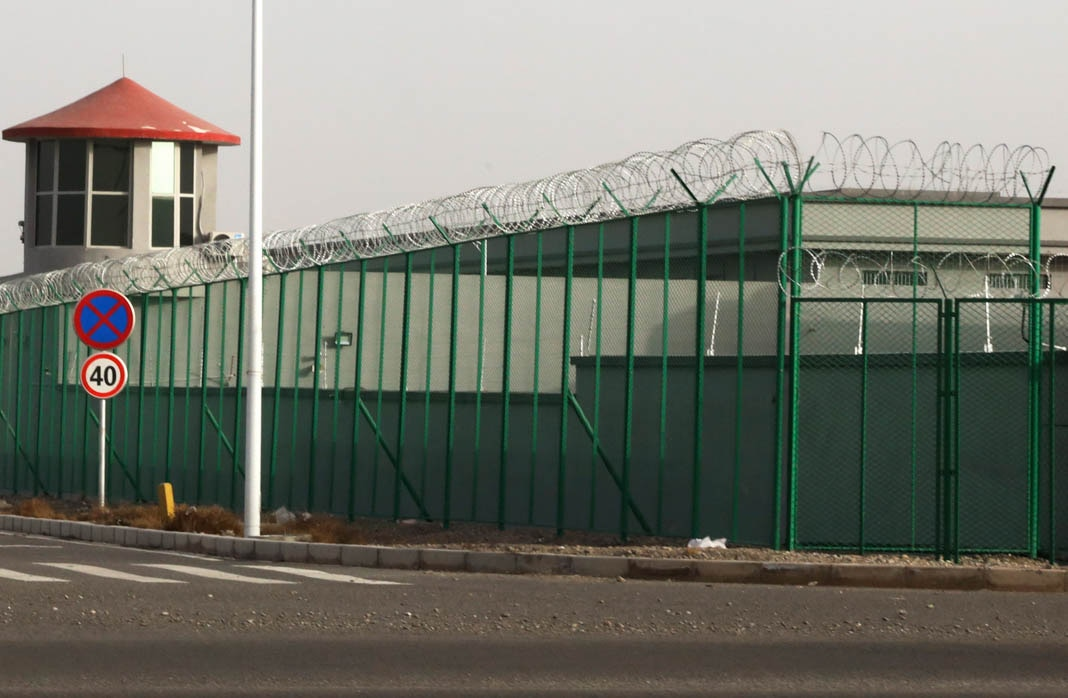 Building with guard tower and barbed wire fence (© Ng Han Gua/AP Images)
