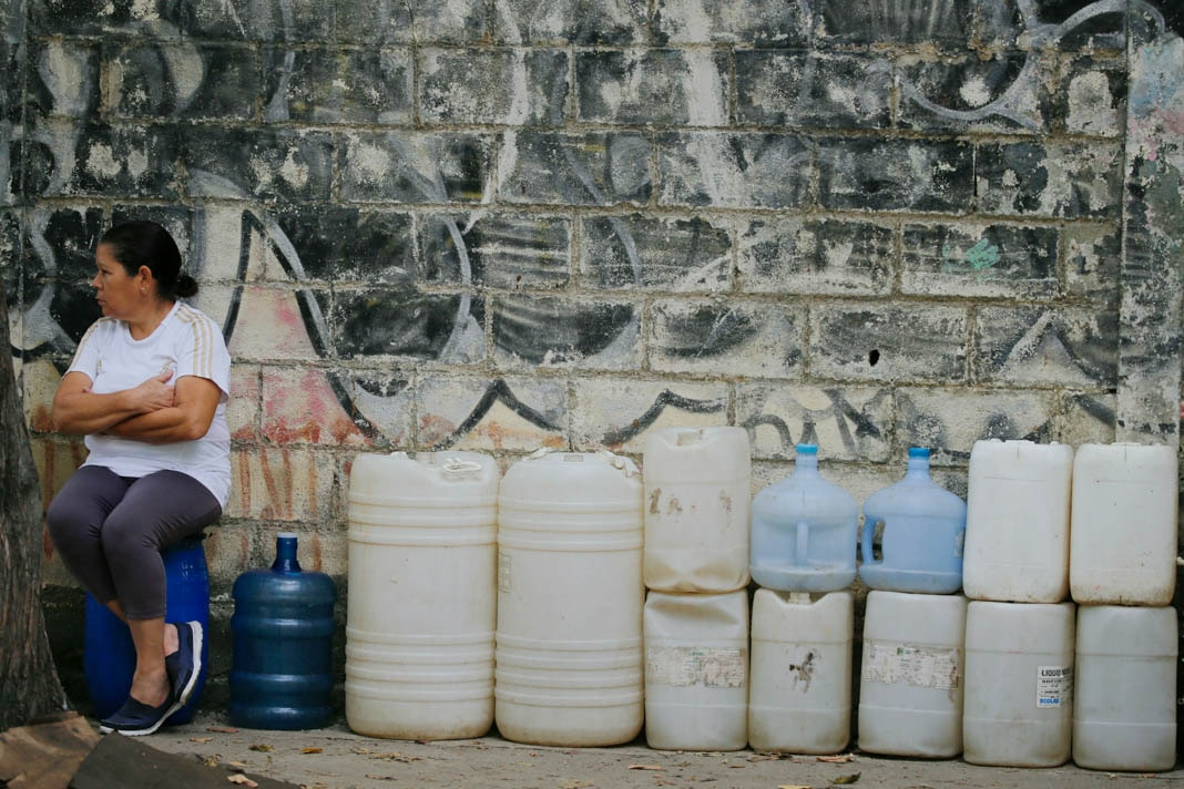 Woman sitting next to empty water containers (© Fernando Llano/AP Images)