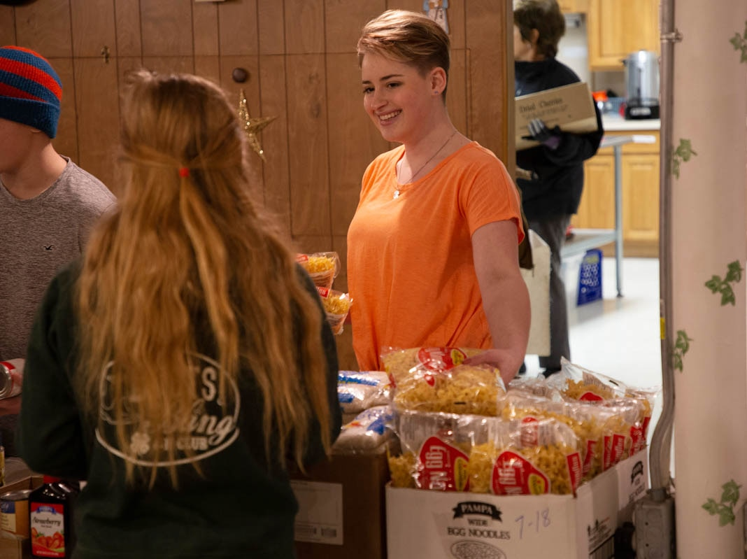 Two women talking with bags of food between them (© 4-H Council)