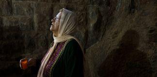 Woman holding candle and looking upward (© Kuni Takahashi/Getty Images)
