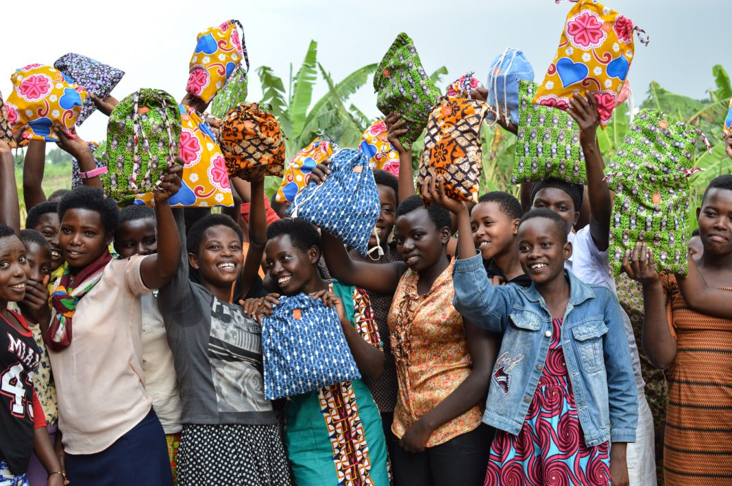 Girls holding up brightly colors cloth bags (© Jeana Nash)
