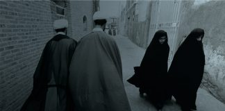 Men and women in long robes in street (© Vahid Salemi/AP Images)