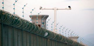 Watchtower and security cameras perched atop a barbed wire wall in China (© Thomas Peter/Reuters)