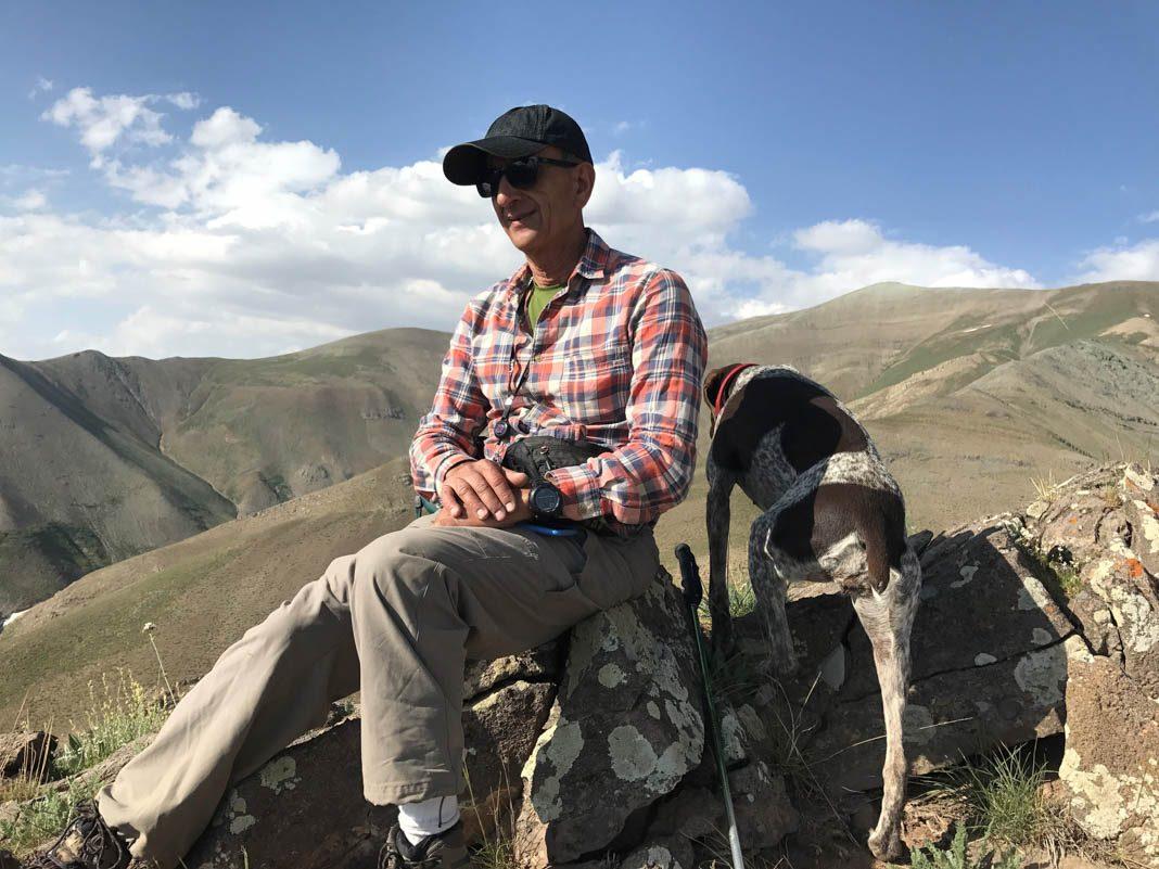 Hombre sentado sobre una montaña junto a un perro (© Reuters)