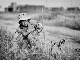 A woman searching for mines in grass (MAG)