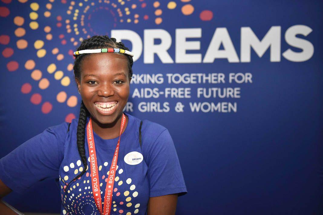 """Una mujer joven sonriente ante un cartel de """"DREAMS"""" (© Francesco Rossi/Pivion/Johnson & Johnson)"""