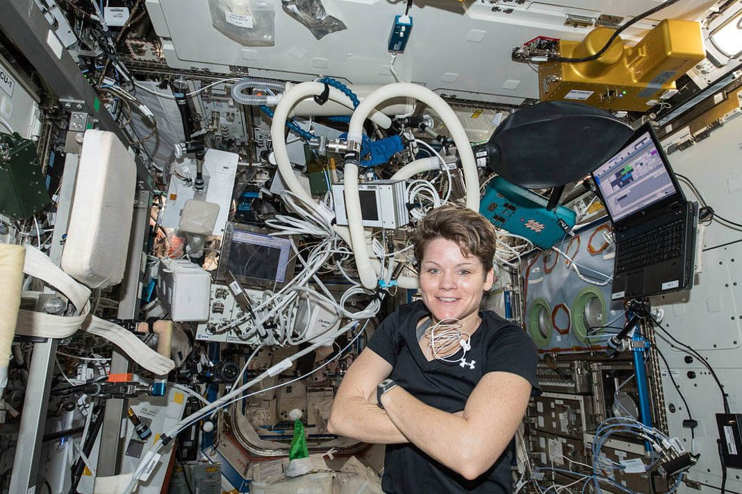 Woman astronaut surrounded by electronics aboard the International Space Station (NASA)