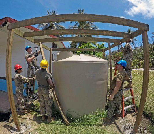 People in uniform building frame around water tank (Mass Communication Specialist 1st Class Tyrell K. Morris/U.S. Navy)