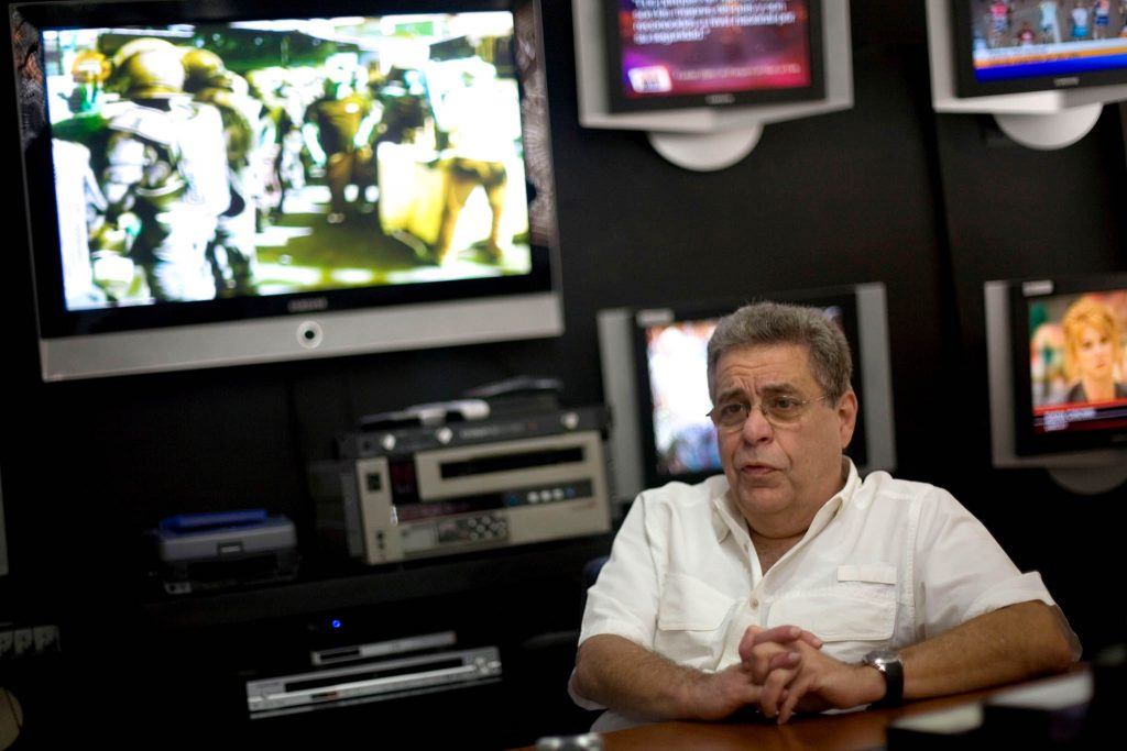 Man seated in front of a bank of televisions (© Ariana Cubillos/AP Images)